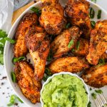 Oven baked chicken wings seasoned with a homemade Cajun spice mix and served with avocado cilantro lime sauce. They're the perfect game day appetizer!