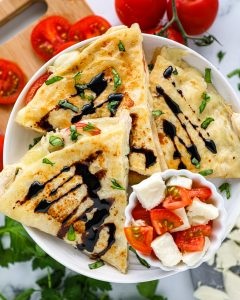 An delicious quesadilla recipe made with shredded chicken, mozzarella, fresh tomatoes, chopped basil and a homemade balsamic glaze! These are perfect for an easy weeknight meal!