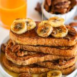 Sourdough french toast made by dipping bread in a mixture of mashed bananas, almond milk, egg and cinnamon. Serve it with sauteed bananas and candied pecans for one delicious breakfast!