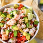 shrimp ceviche in a white bowl topped with avocado and served with tortilla chips