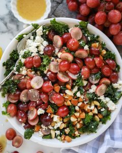 Grape and feta kale salad is a refreshingly light side dish that's just perfect for parties and potlucks! It's only 4 ingredients and is tossed with a lemon dijon vinaigrette too!