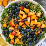 A healthy kale salad recipe made with peaches, blueberries and toasted pepitas! It's light, refreshing and sure to becoming your go-to side dish this summer!