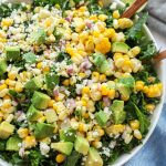 Mexican street corn kale salad topped with avocado and tossed in a creamy cilantro lime dressing in a white bowl sitting next to a blue napking and wood tongs