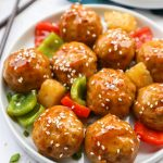 Teriyaki chicken meatballs mixed with canned pineapple and sauteed green and red bell peppers sitting on a white plate sprinkled with sesame seeds