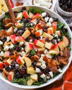 An easy side salad made with fresh apples, crispy bacon, tart cranberries and tender kale all tossed in a sweet maple dressing and sprinkled with creamy goat cheese! It's the perfect salad for fall!
