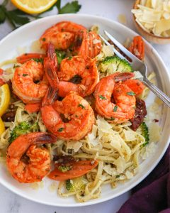 Quick and easy sun dried tomato shrimp topped over lemon basil pesto pasta! It's the perfect meal for a simple weeknight dinner!