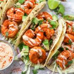 Close up of chipotle lime shrimp tacos with diced avocado and lime wedges