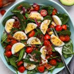 A delicious side salad made with spinach, bacon and eggs that pairs perfectly with any protein you serve for dinner! Plus it's also great for serving a crowd and is always a family favorite!