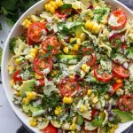 A white bowl filled with cilantro lime pasta salad dressed in a lightened up cilantro lime cream sauce
