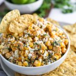 Mexican street corn dip in a small white bowl topped with cotija cheese and served with a platter of chips