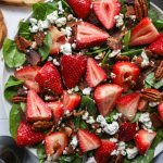 Close up of a strawberry bacon and spinach salad with toasted pecans and goat cheese