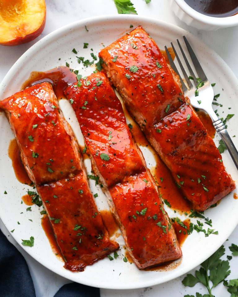Maple bbq salmon on a white plate drizzled with more bbq sauce and sprinkled with parsley surrounded by a white bowl filled with bbq sauce and a blue linen napkin