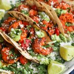 Chili lime shrimp tacos with avocado jalapenoa crema sitting on a white plate served with lime wedges