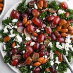 Grape and feta kale salad on a white plate with a silver fork sticking out of it